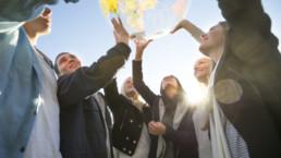 Photo group of people holding a world globe, Global Entrepreneurship Week Switzerland